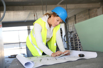 Woman architect on building site using tablet