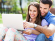 Young couple using laptop outdoors