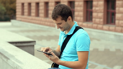 Happy young man playing on a tablet computer in the city center.
