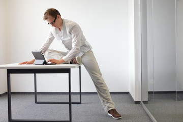 leg exercise during office work - man  with tablet