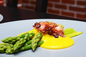Cooked green asparagus with fried bacon chips, Hollandaise sauce