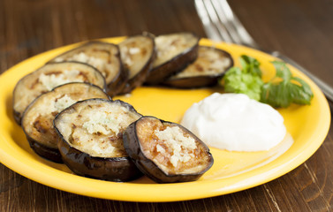 Fried eggplant with garlic and sour cream on a yellow plate.