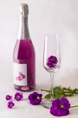 Sektflasche mit Glas und Veilchen