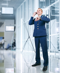 Aircraft pilot talking by phone in airport area