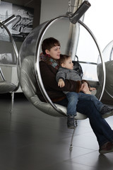 Family relaxes in glass chair
