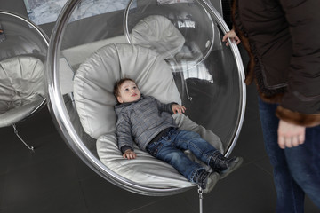 Child resting in glass chair