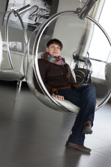 Tourist relaxes in glass chair