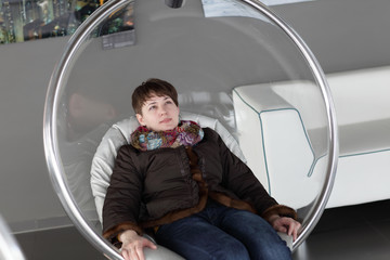 Woman relaxes in glass chair