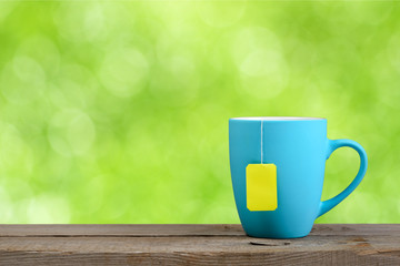 Cup of tea on green nature background