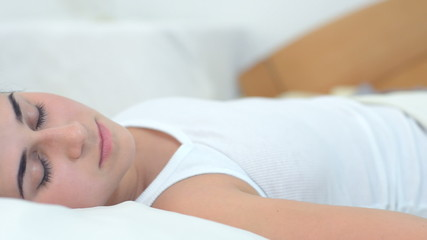 Young beautiful caucasian woman in bed smiling.