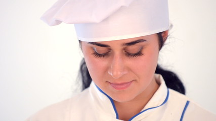 young beautiful female chef on white background smiling
