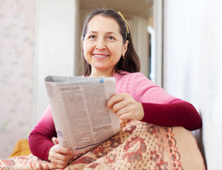 Happy mature woman reads newspaper
