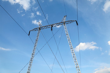 Industry, high voltage electricity pylon with sky and clouds