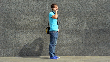 young man walks through city and says on the phone