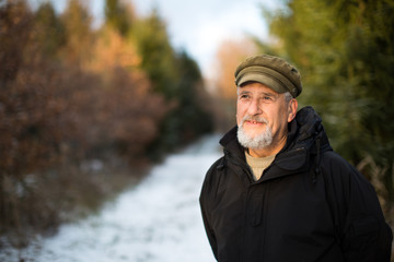 Portrait of a senior man, outdoor on a snowy forest path