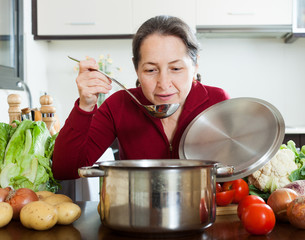 Happy mature woman cooking lent diet soup