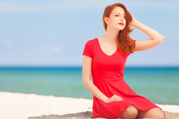 Young redhead girl on the beach.