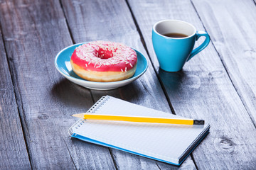 Cup of coffee with notebook and donut.