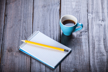 Cup of coffee witn notebook and pencil, on wooden table.