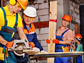 Group people  builder with circular saw .