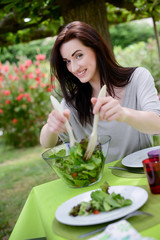 cheerful cute young woman eat salad at barbecue party
