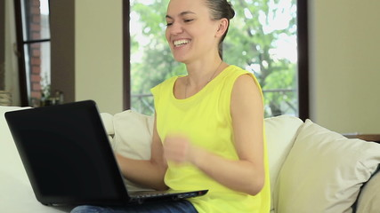Excited woman sitting on sofa at home with laptop