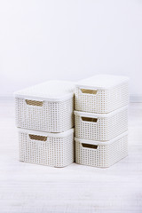 Plastic baskets for storing things in floor on room background