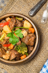 Hearty beef stew in wooden bowl
