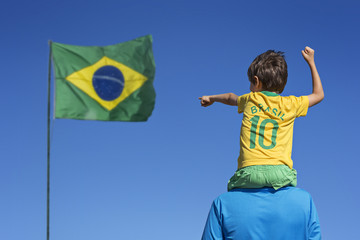 Boy and his father looking up at the Brazilian flag
