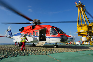 The helicopter landing officer is going to helicopter at oil rig