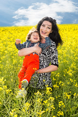 Laughing mother and son in canola field