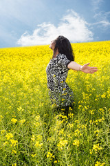 Happy woman in rapeseed field