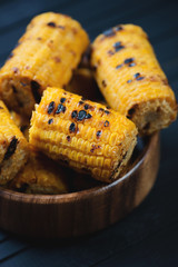 Grilled sweet corn in a wooden bowl, close-up, vertical shot