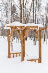 wooden kiosk covered by snow