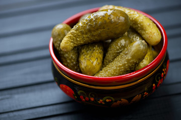 Khokhloma bowl with pickled cucumbers, black wooden background
