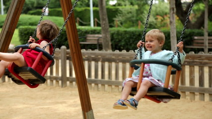 Laughing girls on swing in summer park