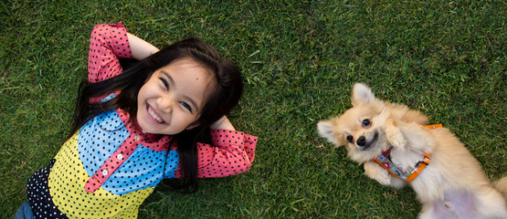 Happy Asian girl with her doggy portrait lying on lawn