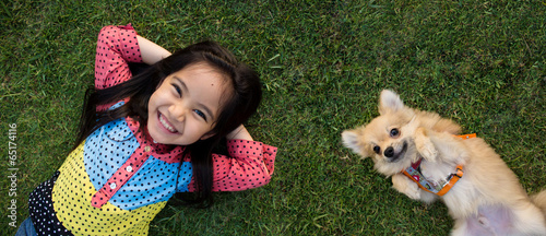 Happy Asian girl with her doggy portrait lying on lawn - 65174116