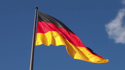 German flag of Germany floating in the wind, blue sky