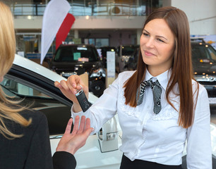 Happy saleswoman handing over car keys to young female