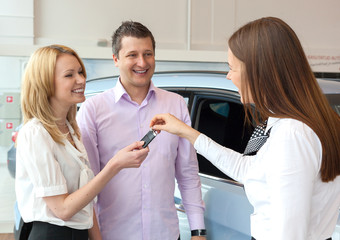 Happy saleswoman handing over car keys to young family
