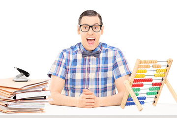 Man sitting on a table with abacus and pile of documents