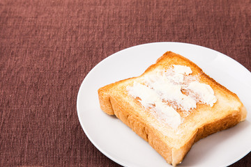 toast and butter that is placed on a dish