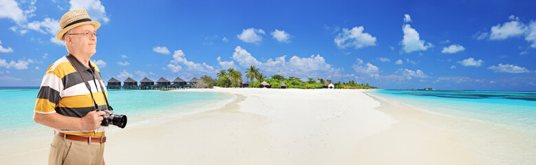 Panoramic view of a male tourist standing on a tropical beach at