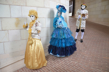 Three persons in Venetian masks and costumes