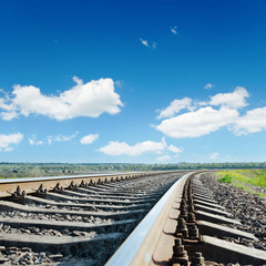 railroad to horizon under blue cloudy sky