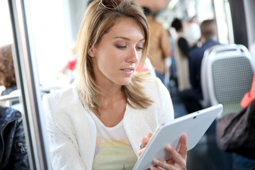 Woman in city train websurfing with tablet