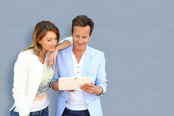 Mature couple on grey background using tablet