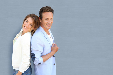 Funny mature couple standing on grey background