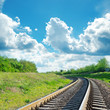 green landscape with railroad to horizon and blue sky with cloud